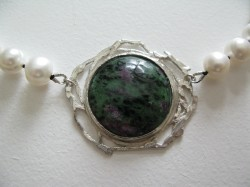 detail showing stone pendant from pearl necklace